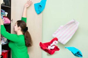 Woman pulling things out of a closet